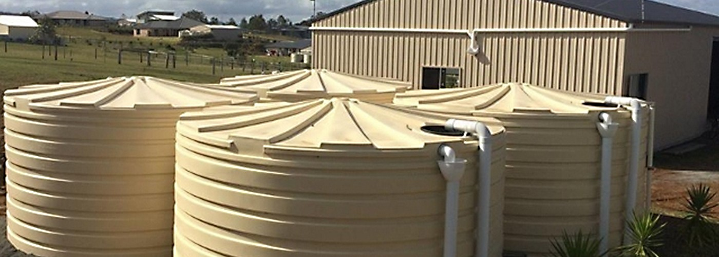 An image of 3 beige water tanks in front of a house as part of a blog about saving water during the summer months