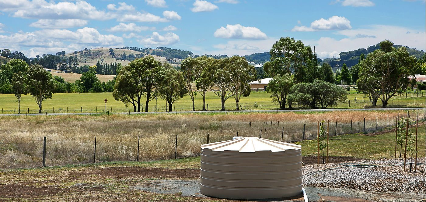 A cream coloured water tank siutated in a paddock with landscape behind it